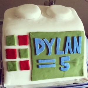 "Lego computer cake with green screen and ""Dylan = 5"" written in blue fondant"